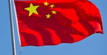33784466 - chinese flag with flag pole waving in the wind over blue sky background.